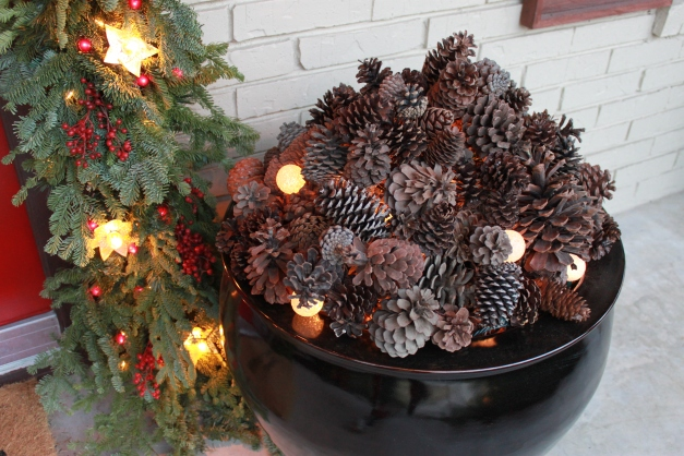 Pinecones and twinkly lights piled high in a black fishbowl