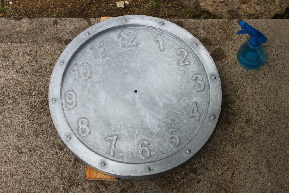 Galvanized Clock Coated in White Vinegar Sitting in th Sun