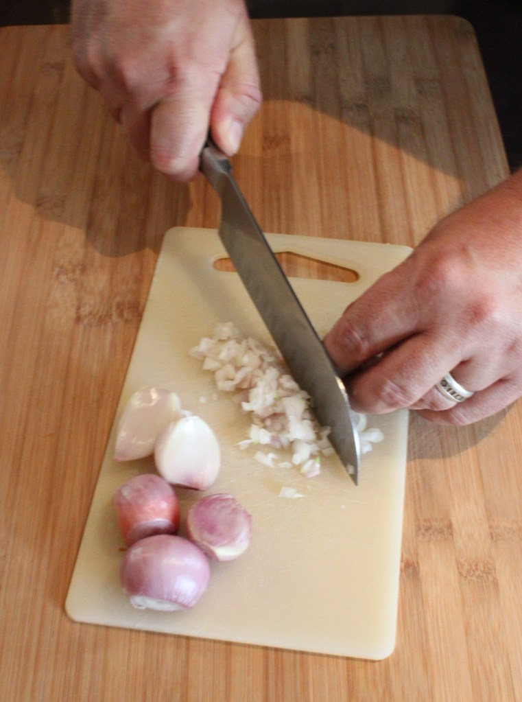 Finely Dice Shallots on A Plastic Cutting Board