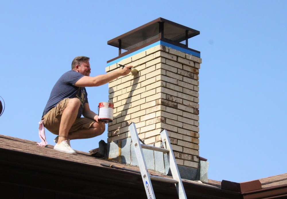 James Painting the Chimney to Match the Rest of the House