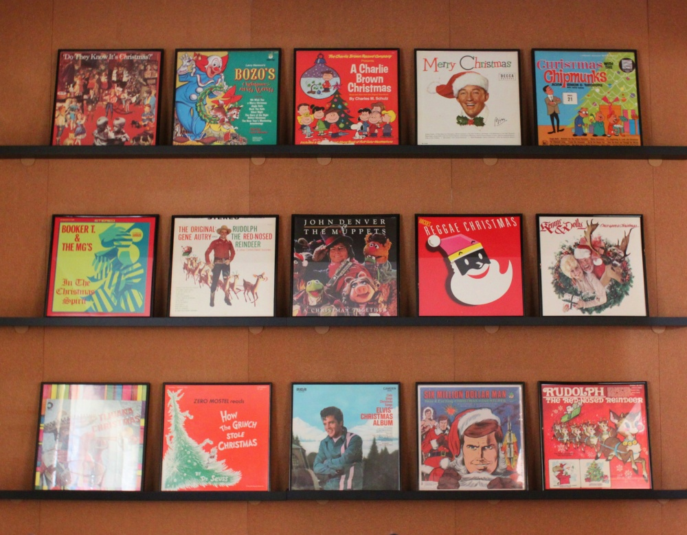 Wall of Framed Holiday Records in the Cavender Diary Living Room