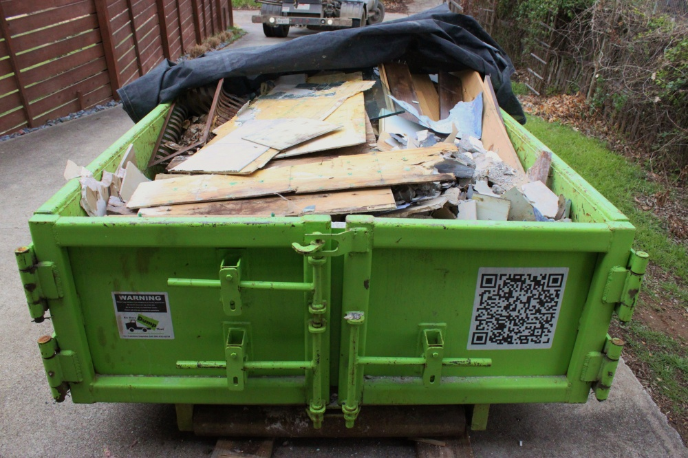 Green Dumpster Filled with all the Bathroom Debris