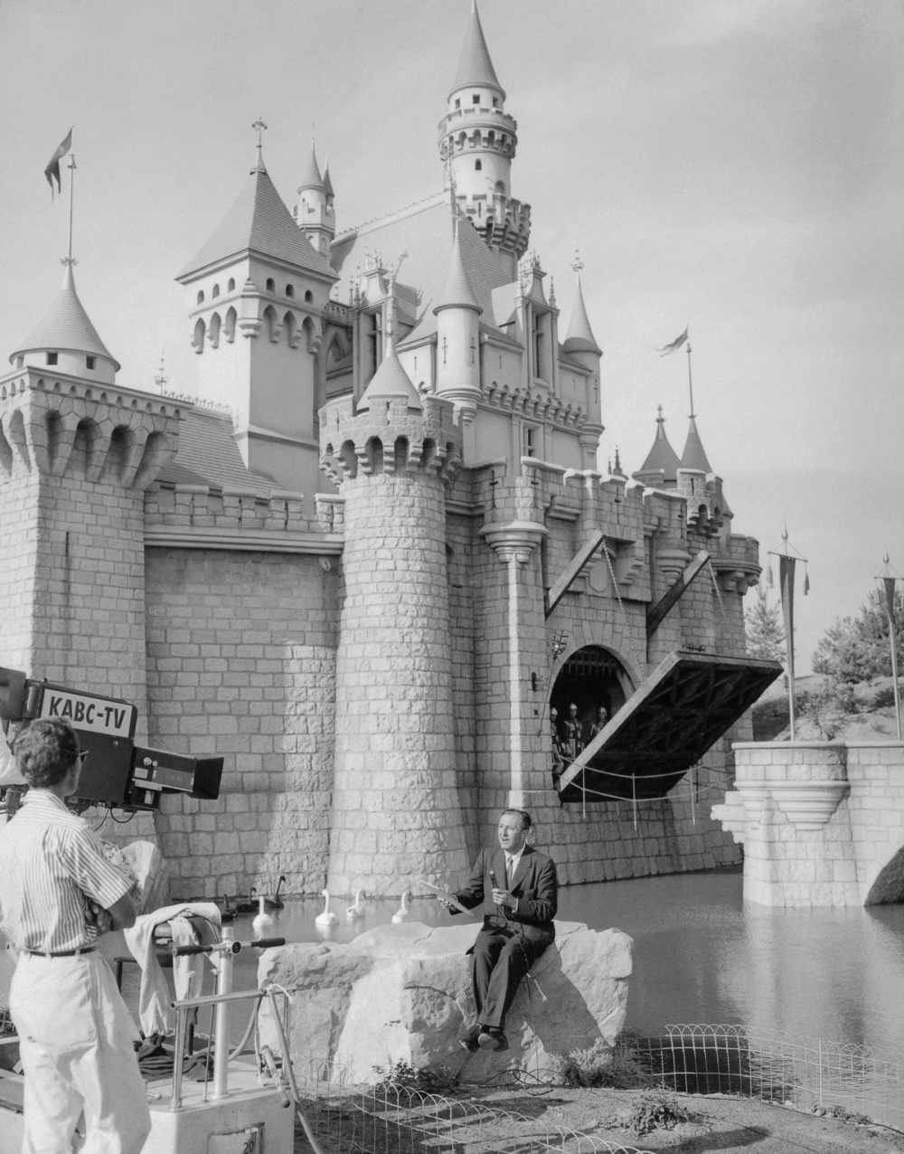 18 Jul 1955, Anaheim, California, USA --- Original caption: Walt Disney, the cartoonist-producer and lately creator of Disneyland, the 160-acre, $17,000,000 playground for children, sits in front of his Fantasyland castle during a telecast of the official opening of the playground. The premiere was televised nationally. --- Image by © Bettmann/CORBIS